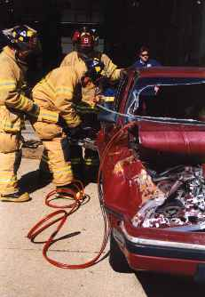 A team of firemen demonstrating the jaws of life.